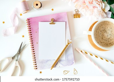 Top view of white working table background with planner. Flat lay scissors, tapes, peonies, golden paper binder clips, blank greeting card, Notebook and pen. Desktop mock-up, handmade tools.