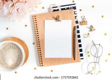Top view of white working table background with cup of coffee and planner. Flat lay glasses, flower, golden paper binder clips, blank greeting card, craft Notebook and pen. Desktop mock-up scene.