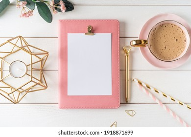 Top view of white working table background with blank paper notebook, cup of coffee. Flat lay green leaf, flowers, golden paper binder clips. Notepad and pen. Desktop mockup, workspace, stationery.
