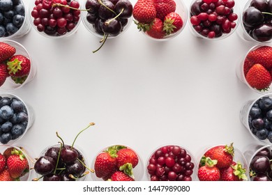 top view of whole cranberries, strawberries, blueberries and cherries in plastic cups on white background