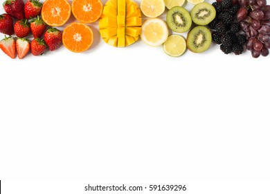 Top view of whole fruits and in the rows; red, orange, yellow, green fruits on the white background; grapefruit, mango, strawberries, orange, lemon, kiwi