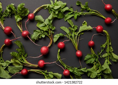 top view of whole tasty radish with green leaves on black background