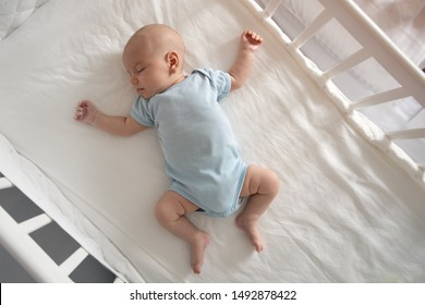 Top view wide angle sleeping newborn baby lies in a crib arms and legs outstretched, baby sleep