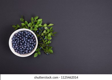 Top view of wild organic blueberries with green leaves in a white bowl on black background with copy space. Flat lay.