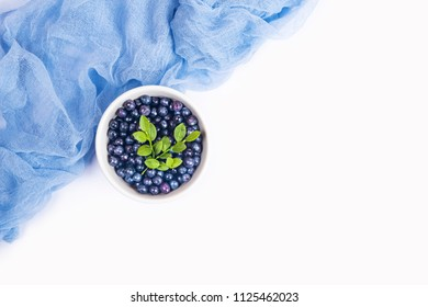 Top view of wild organic blueberries in a white bowl decorated with light blue colorful gauze fabric isolated on white background with copy space. Flat lay.