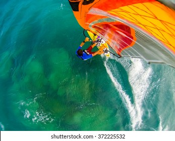 Top view of windsurfer gliding over cristal clear water and reef