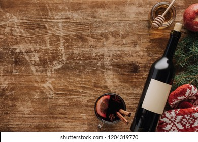 top view of wine bottle, cup of mulled wine and honey on wooden tabletop, christmas concept