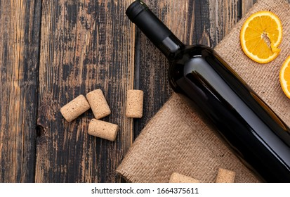 Top view wine bottle on sackcloth with copy space on dark wooden background horizontal