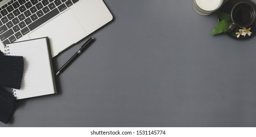 Top view of winter workspace with laptop computer and office supplies on grey desk background