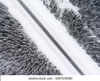 Top view at wintry slippery road passing through the snow covered coniferous forest, diagonal view
