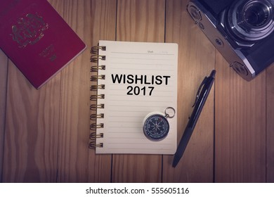 Top view of WISH LIST 2017 written on the notebook,travel planning concept.note book,compass,passport,film camera on the wooden desk.