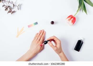 Top view of woman applying serum on her hand with pipette on white background. Female hands testing cosmetic on table with scale, litmus paper, flower and leaves.