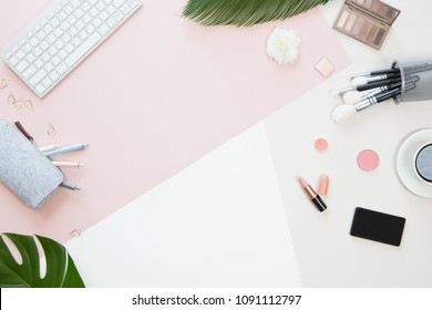Top view of woman beauty blogger working desk with computer keyboard and laptop, notebook, decorative cosmetic, flowers and palm leaves, envelope on pink and white pastel table. Flat lay background.