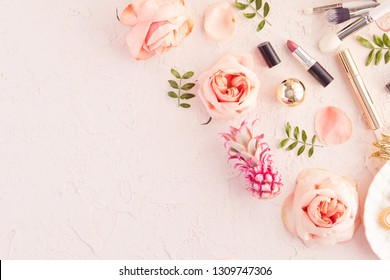 Top view of woman beauty blogger working desk with decorative cosmetic, flowers and palm leaves, leaf plate, envelope on pink pastel table. Flat lay background with copyspace.