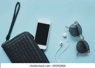 Top view of woman black bag open out with accessories smartphone, earphone and sunglasses on blue background.