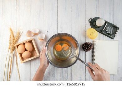 Top view of woman chef breaking an egg into the  bowl. Female chef whisking eggs in bowl on white table