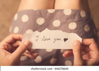 Top view of woman in dotted dress holding a paper message with the text I love you