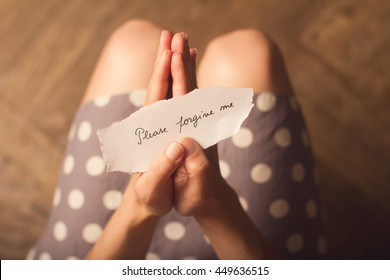 Top view of woman in dotted dress holding a paper message with the text please forgive me