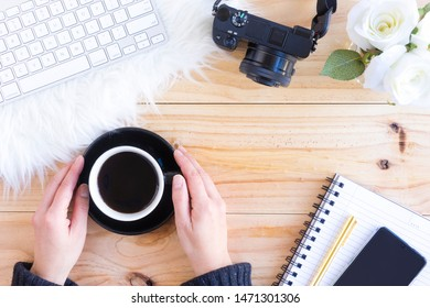 Top view of woman enjoying coffee with camera, keyboard, notepad and phone on wooden table in home office.