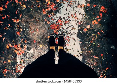 Top view of woman feet in black clothes stand outdoor yard with orange petals fall in raining day