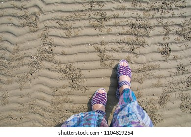 Top view of woman feet with colorful sandal walking on the beautiful wavy sand on sea beach with crab hole with copy space