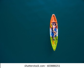 Top view of woman floating on the kayak at the deep blue lake. Aerial view of woman kayaking on the big lake. Cheow Lan lake, Surat Than, Thailand.