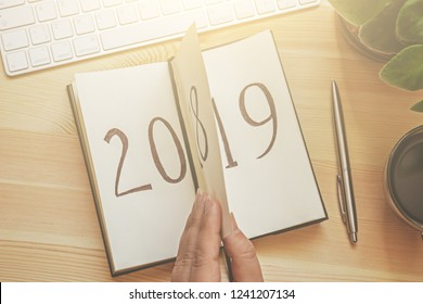 Top view of woman hand flips notepad sheet on wooden table with keyboard and cup of coffee. 2018 is turning, 2019 is opening, toned with light effect