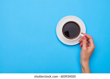 Top view of woman hand holding a cup of coffee over flatlay