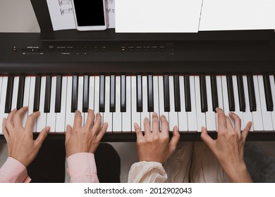 Top view of woman hand playing paino together, music teaching, practicing, education. some hand blurred by movement. Note sheet and smartphone on paino holder.
