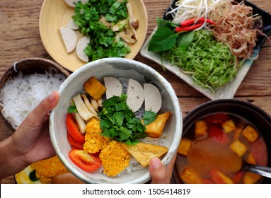 Top view woman hand prepare homemade breakfast, vegan rieu noodle soup or vegetarian crab paste vermicelli soup, a traditional Vietnamese dish, plate of vegetables, herbs, soup pot, ready to eat
