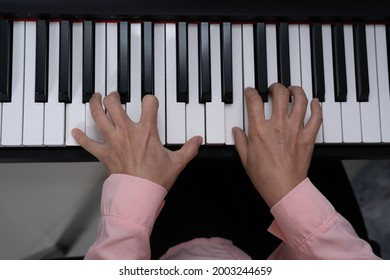 Top view of woman hand pressed on paino keyboard, playing paino, artist practicing music.