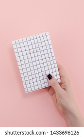 Top view of woman hand with stylish black manicure holding notepad with copy space on pink color paper background in minimal style. Template for feminine blog social media