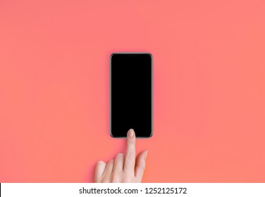 Top view of a woman hand using phone on Living Coral color background