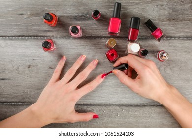 Top view to woman hands, applying coat of red nail varnish on her nails, with lot of nail polish on gray wood desk in background.