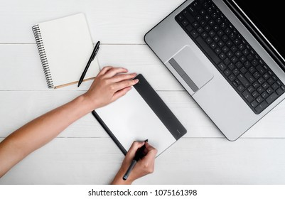 Top view of woman hands with graphic tablet drawing and retouching image on laptop computer, using digital tablet and stylus pen, free space. Graphic designer working on digital tablet. Blank notebook