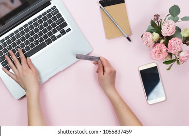 Top view of woman hands holding credit card, online shopping concept, workspace with laptop, mobile phone, flowers and notebook, flat lay.