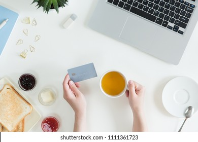 Top view of woman hands holding credit card, business lunch concept, online shopping, workspace with laptop, mobile phone, flowers and notebook, toast, flat lay.