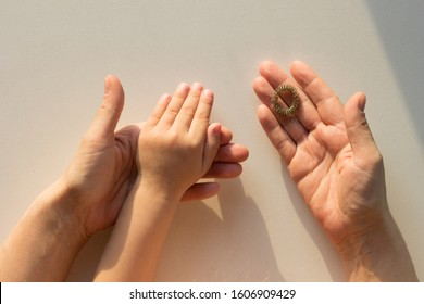 Top view of woman hands holding child hand and massage ring Su-Jock on white background