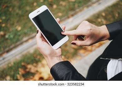 Top view of a woman hands holding white smartphone with blank screen