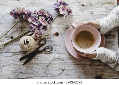 Top view of woman hands holding hot coffee cup, handmade crafts