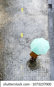 Top view of woman hidden under umbrella is walking on street under rain drop