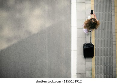 Top view of woman holding smart phone and luggage while going to the station/airport.