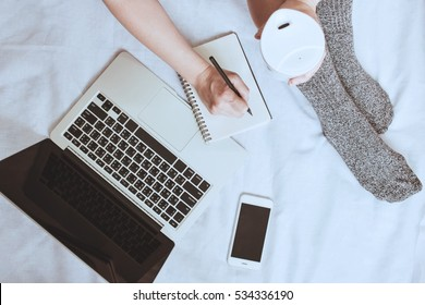 Top view of woman legs in socks and writing notebook with laptop and smartphone on cozy bed