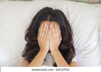 Top view woman is lying on her bed. She is covering her head with her hands, feeling sad or depressed. (advertise concept)