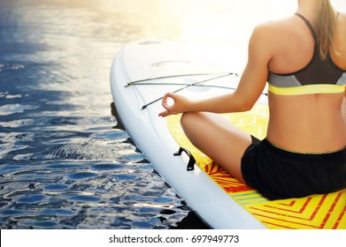 Top view of woman making  mudra gesture sitting on paddle board