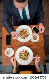Top view woman and male eating portions of salad after working day. They situating at desk. Dinner concept