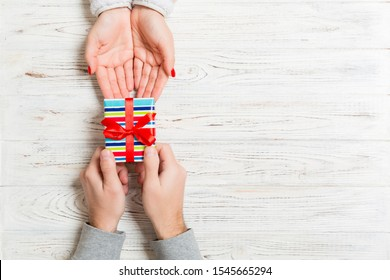Top view of a woman and a man giving and receiving a present on wooden background. Love and relationship concept. Copy space..