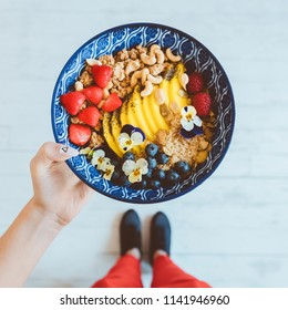 Top view of woman photographing healthy lunch bowl aganist white floor. Unrecognizable person, close up of bowl.