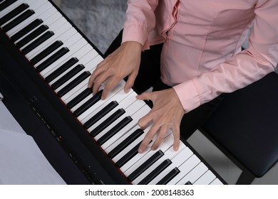 Top view woman playing paino, hand pressed on key, artist practicing music. with part of blank sheet note on note paper holder.
