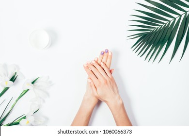Top view woman putting nutritious cream on her hands on white background among jar of cosmetic cream, flowers and palm branch. Final stage of manicure: woman uses moisturizer for the skin. Copy space.